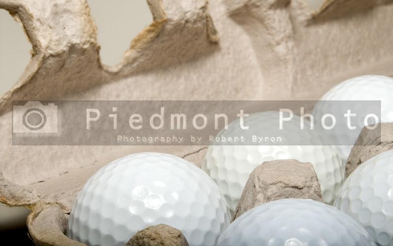 Several golf balls in an egg carton.