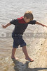 A young boy playing at the seashore.