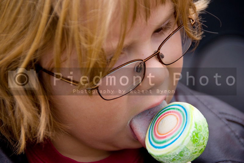 A young boy eating a jaw breaker on a stick.