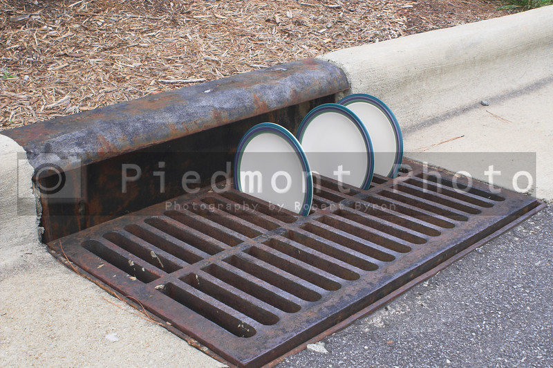 Plates drying in a storm drain grate.