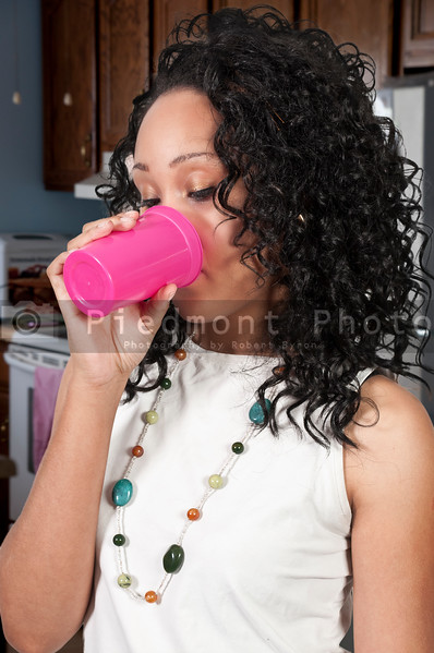 A beautiful young black woman drinking juice or milk or water in the morning