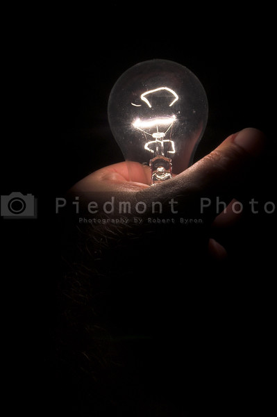 A person powering a light bulb by holding it.