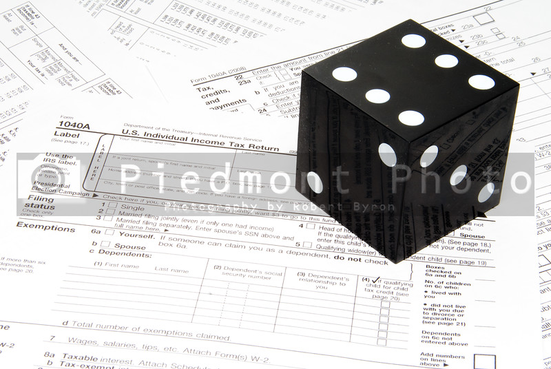 A giant die on a stack of tax forms.