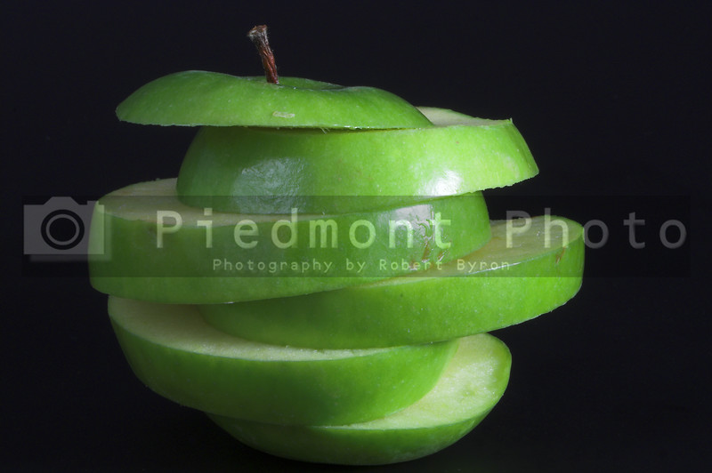 A sliced green apple in a stack.