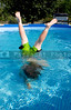 A little boy doing a handstand in a pool.