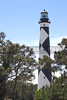 A historic lighthouse guiding ships away from rocky shoals.