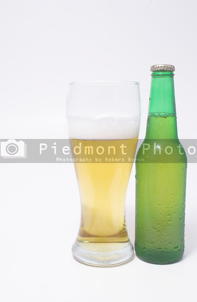 A pilsner glass of beer and a beer in a bottle.
