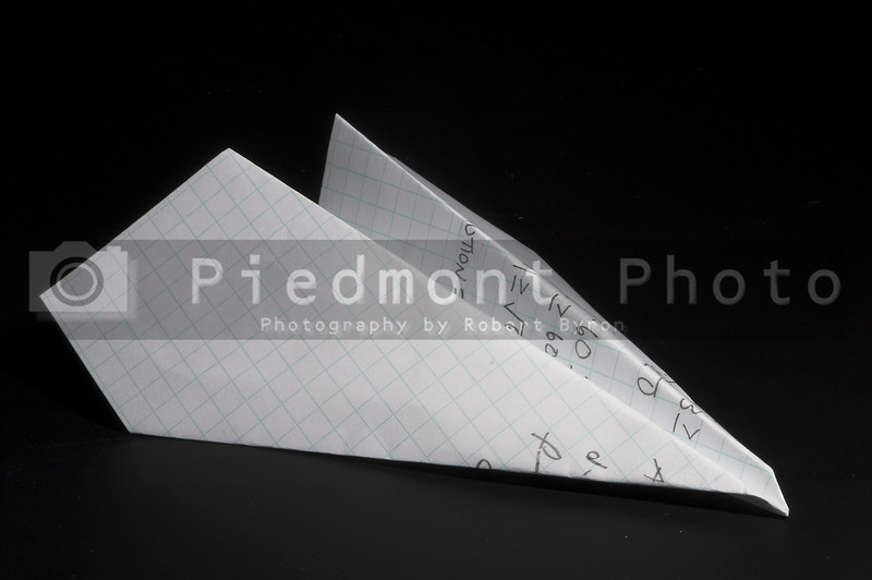 A paper airplane made out of a homework paper.