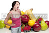 A beautiful woman standing in front of a wide assortment of delicious and fresh fruits