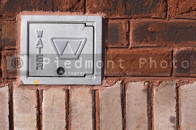 The cover to a water meter supplying water to the masses.
