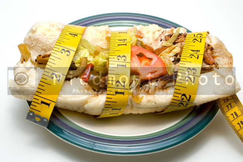 A steak submarine sandwich loaded with vegetables.