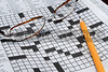 A Crossword Puzzle, pencil and a set of reading glasses.