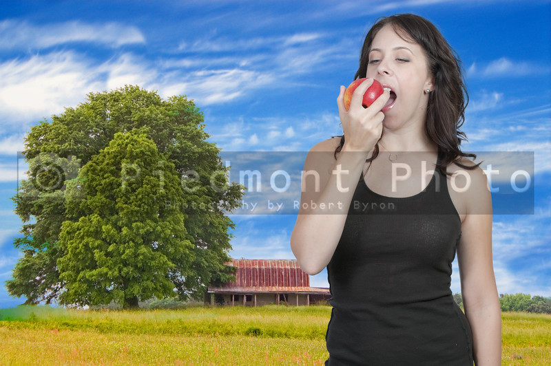 A beautiful young woman eating a frsh delicious apple