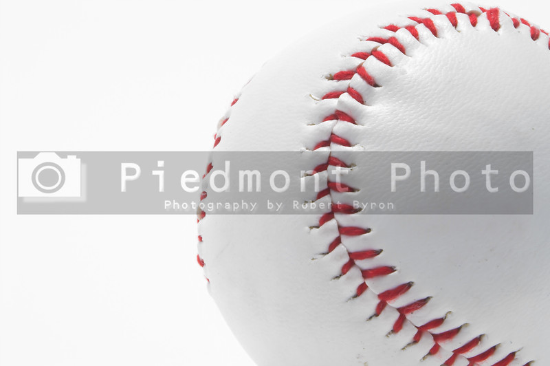 A lone baseball with bright red stitching.