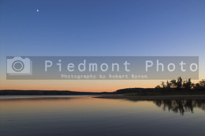 A beautiful sunset over a lake with the moon rising.