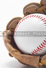 A baseball inside of a baseball glove.
