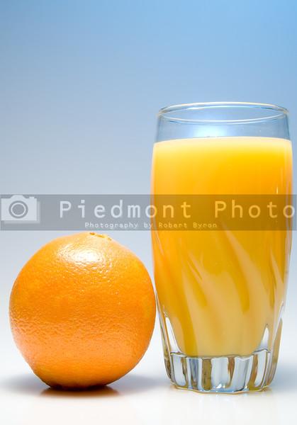 A glass of orange juice with an orange.