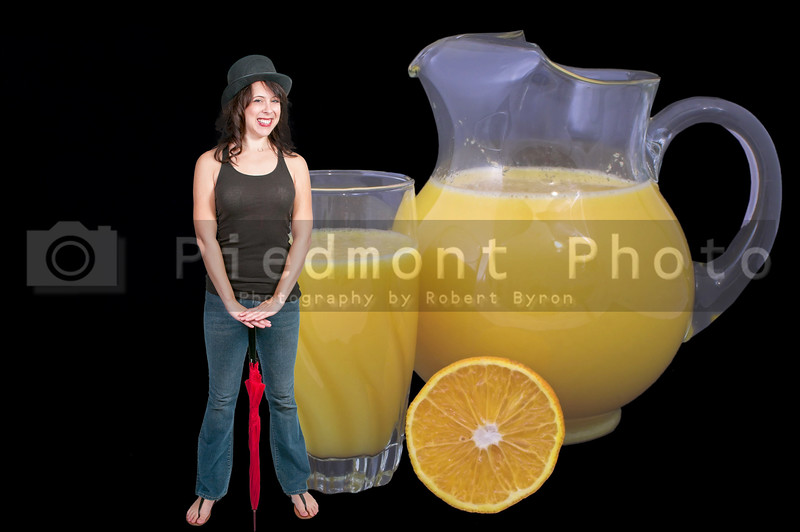 Orange juice in a pitcher and drinking glass with orange slices.