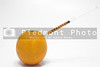 An orange being injected with juice from a syringe.