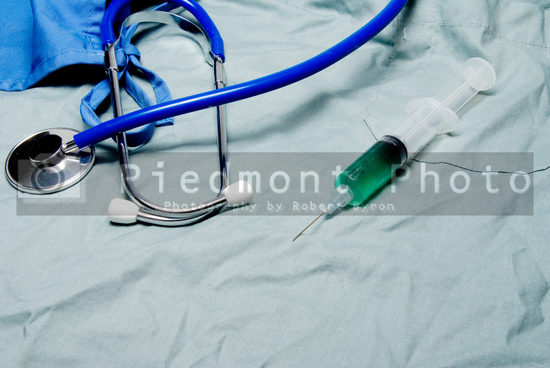 A medical syringe, stethoscope, latex free gloves and scrubs.