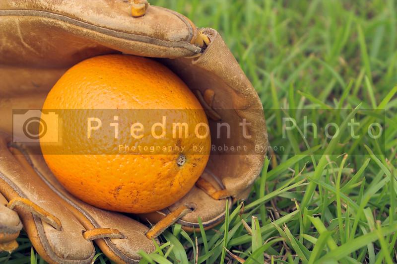 A delicious orange in a baseball glove.