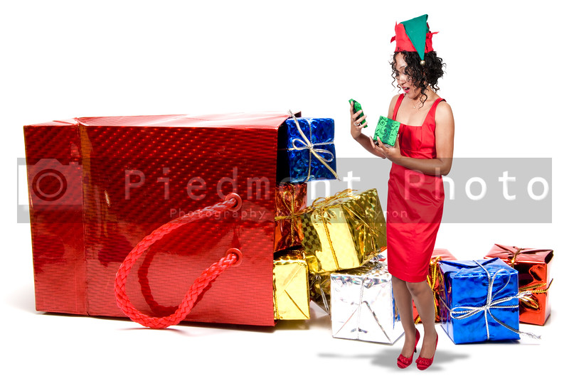 A beautiful young black woman opening a Christmas present