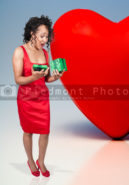 A beautiful young black woman opening a Valentines Day present