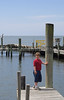 A young boy standing on a pier.
