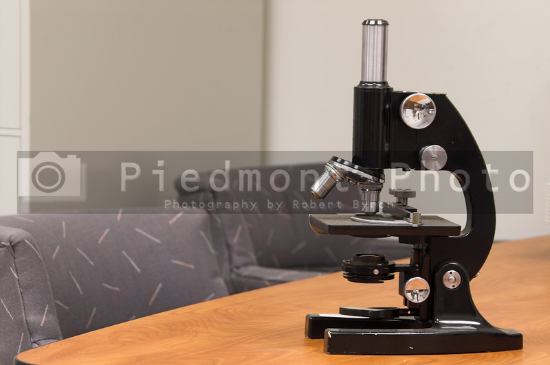 A precision tabletop microscope on a conference table.