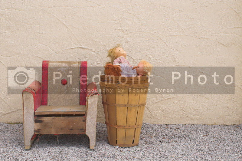 An old antique chair and a basket of old dolls.