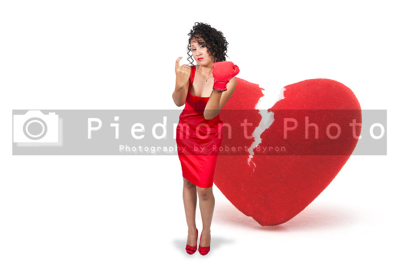A beautiful black woman in a red dress wearing a boxing glove in front of a broken heart
