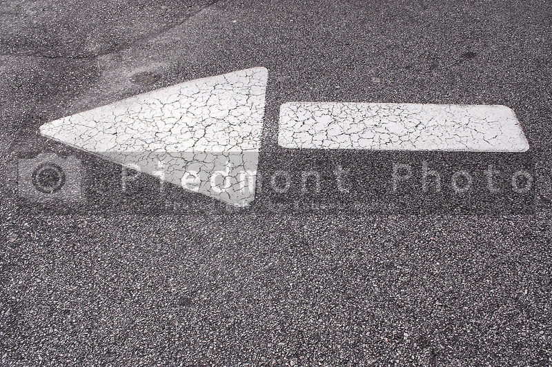 The directional arrow on the pavement of a parking lot.