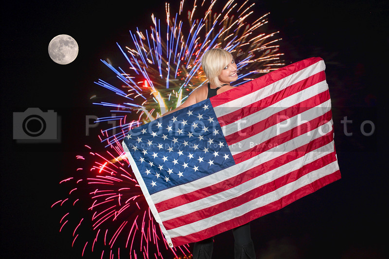A beautiful young woman holding an American flag during a fireworks display during a full moon