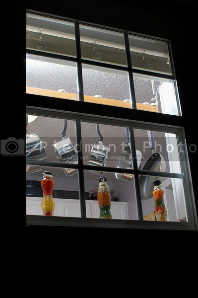 Pots and pans hanging in a kitchen window.
