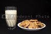 A plate full of chocolate chip cookies and a glass of milk.