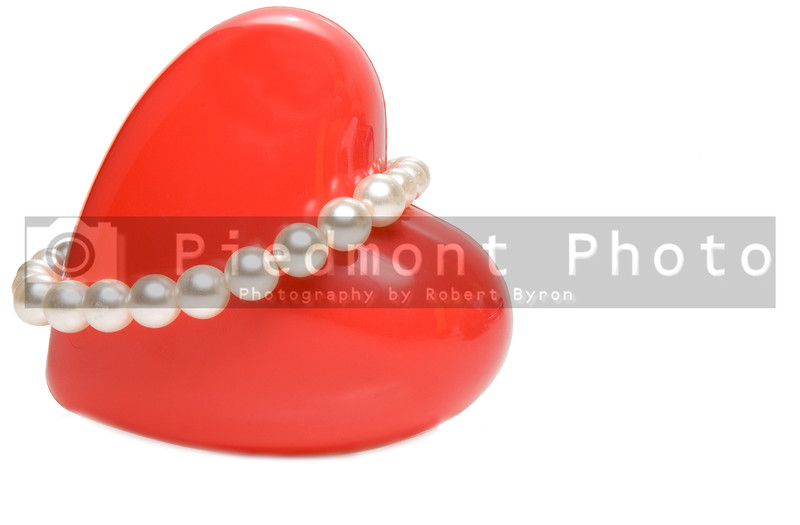 A red valentines heart wrapped in pearls.
