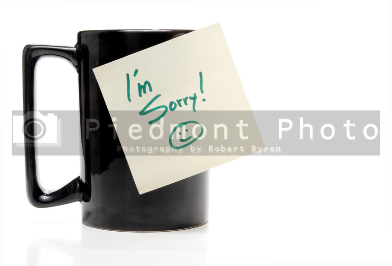 A coffee mug with an Im Sorry note.