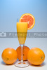 A glass of orange juice with an umbrella and slice.