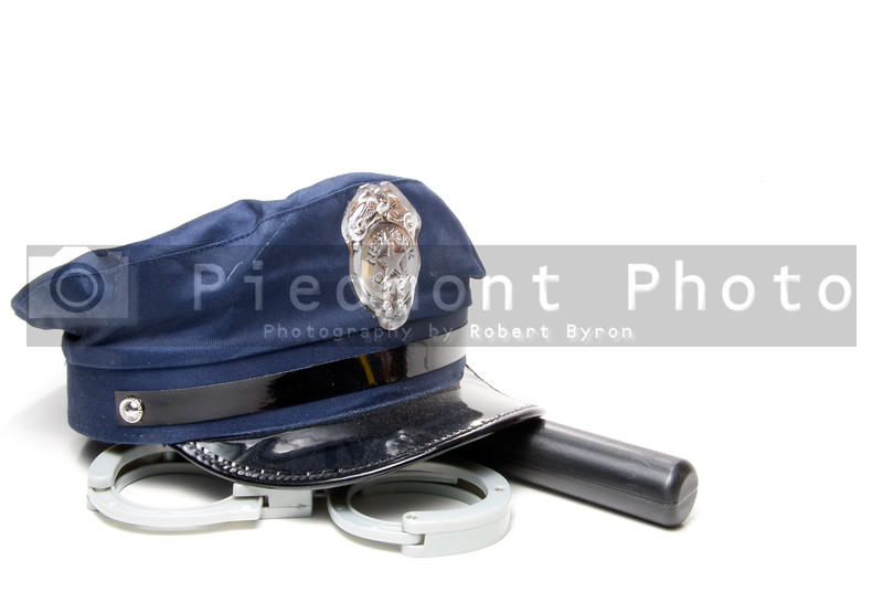 A police hat, night stick and hand cuffs.