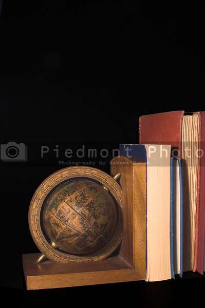 A globe on a bookend holding up books.