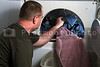 A man taking laundry out of a clothes dryer.