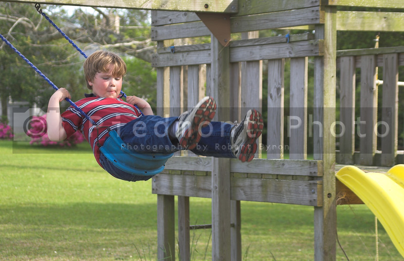 A young boy swinging on an outdoor swingset.