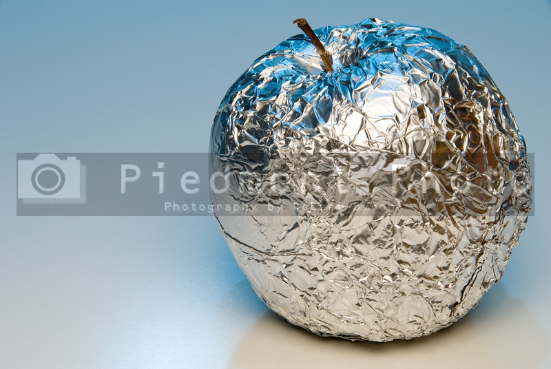 A fresh apple covered in aluminum foil.