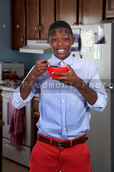 Handsome teenager eating food from a bowl