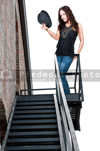 Beautiful young woman in a fedora hat on a fire escape