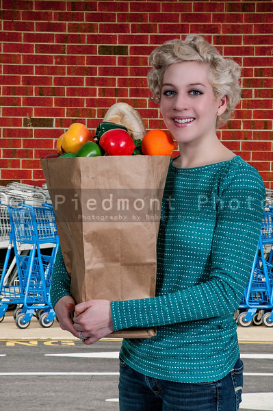 Beautiful woman grocery shopping holding a brown paper bag
