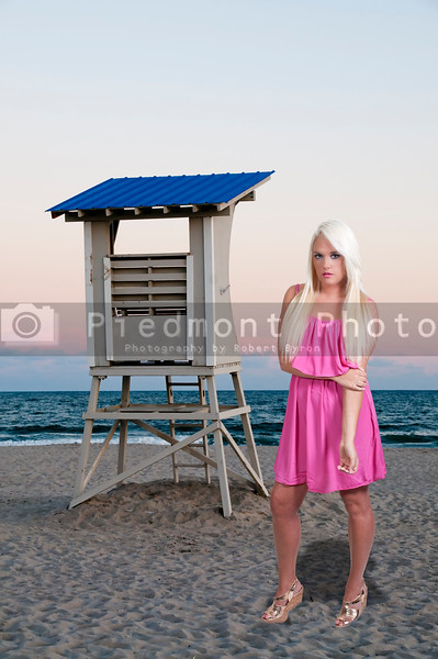A beautiful young woman on the beach by a lifeguard station