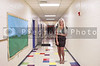 Beautiful young woman teacher at a grade elementary school hallway