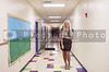 Beautiful young woman teacher at a grade elementary school hallway