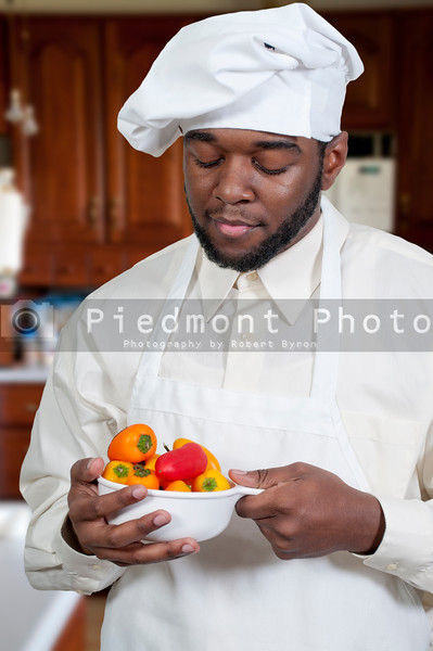 Black African American male chef holding a bowl of fresh sweet peppers